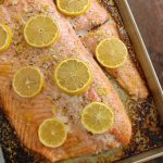 Baked Salmon with Lemon-Dill Sauce on a baking sheet facing left