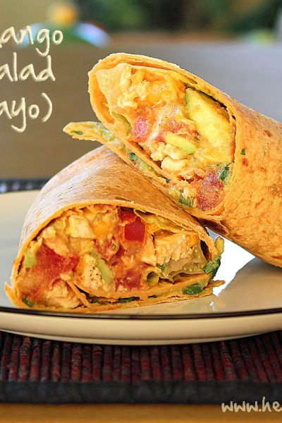 """The words """"Tomato and Mango Chicken Salad Wrap (no mayo)"""" above a photo of the wrap on a white plate"""