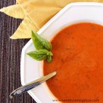 Roasted Tomato Soup in a white bowl with a spring of herbs