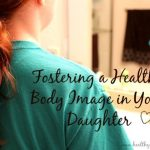 "The words ""Fostering a Healthy Body Image in Your Daughter"" over a photo of a girl looking in a mirror"