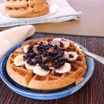 A waffle on a blue plate with bananas and blueberries
