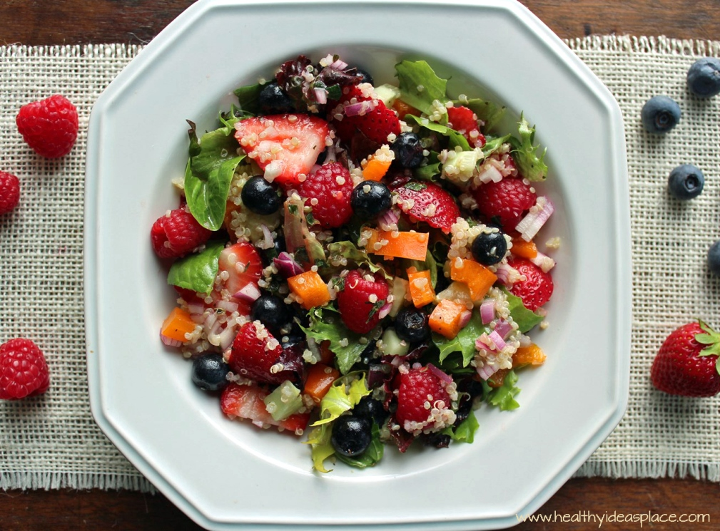 Triple Berry and Quinoa Salad with Mixed Greens places sweet berries and nutty quinoa amidst a backdrop of earthy mixed greens, cucumbers, and peppers, all pulled together with a balsamic vinaigrette for a colorful and scrumptious salad.