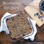 Blueberry Oat Bars in a clear baking dish next to a colander containing blueberries