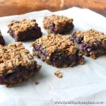 six Blueberry Oat Bars sitting on white paper