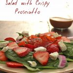 "Strawberry and Spinach salad on a plate with the words ""Strawberry Spinach Salad with Crispy Prosciutto"""