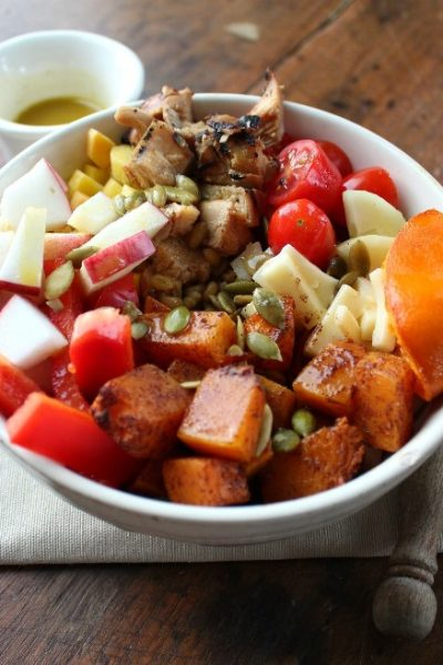 Fall Salad Bowl with Roast Butternut Squash in a white bowl with container of vinaigrette in the background