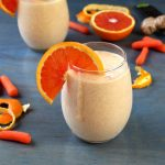 Orange and Carrot Smoothie with Ginger and Turmeric with ingredients on blue background
