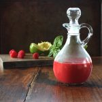 Raspberry Basil Vinaigrette in a cruet in front of cutting board containing the recipe ingredients
