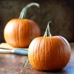 Two small pumpkins sitting on a wooden table with a knife