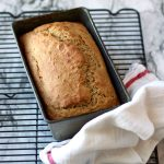 Banana bread in the pan on a cooling rack with a towel