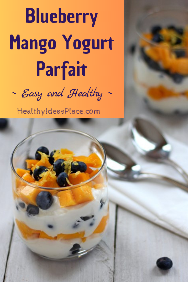 Diced mango and fresh blueberries layered with Greek yogurt in a clear glass