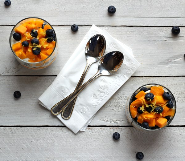 Top view of diced mango and fresh blueberries on top of Greek yogurt in a clear glass