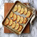 Toasted crostini on pan sitting on cutting board