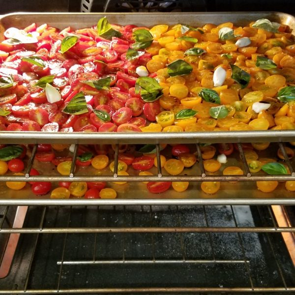 Two pans of grape tomatoes in an oven