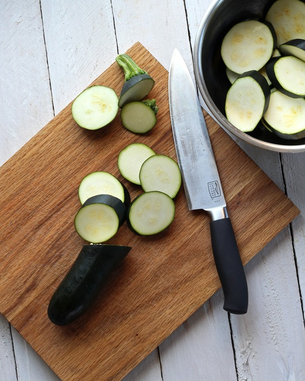zucchini being sliced on wooden cutting board