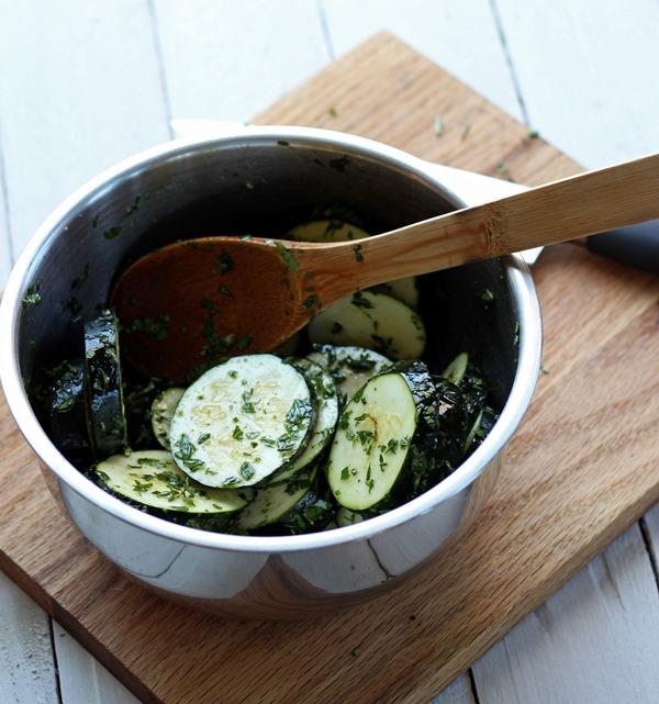 sliced zucchini and chopped fresh herbs in a metal bowl on a wood cutting board