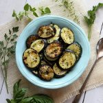 Grilled zucchini slices in a teal colored bowl