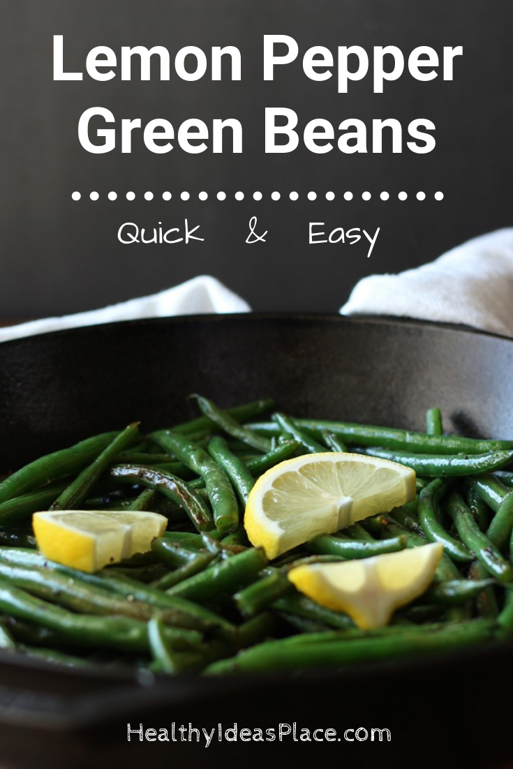 green beans and lemon slices in skillet with dark background