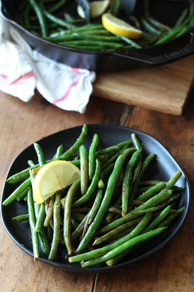 Cooked green beans on black plate with lemon slice