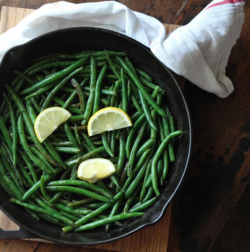Green beans in dark skillet with lemon slices