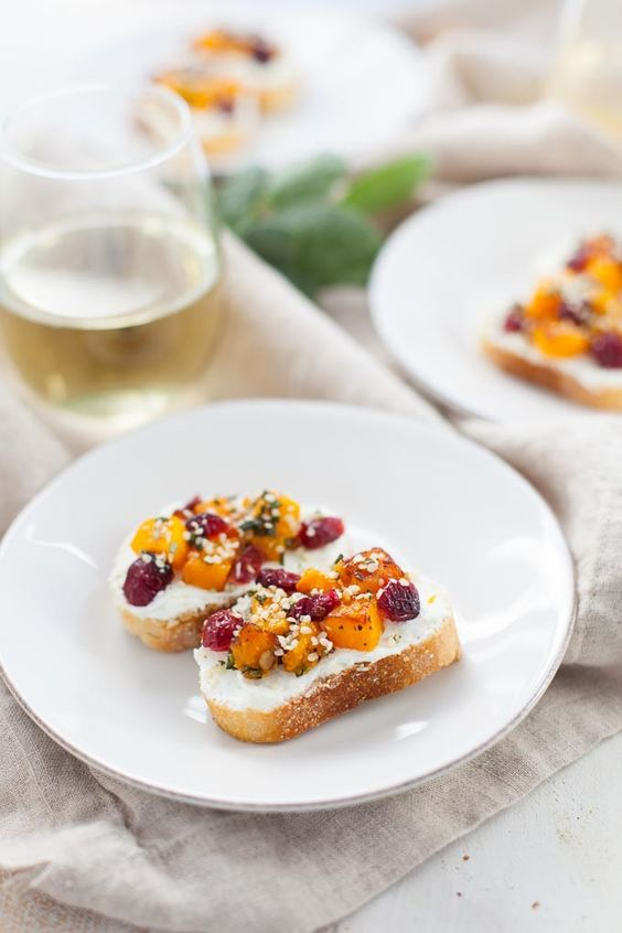 crostini topped with cranberries on white plate