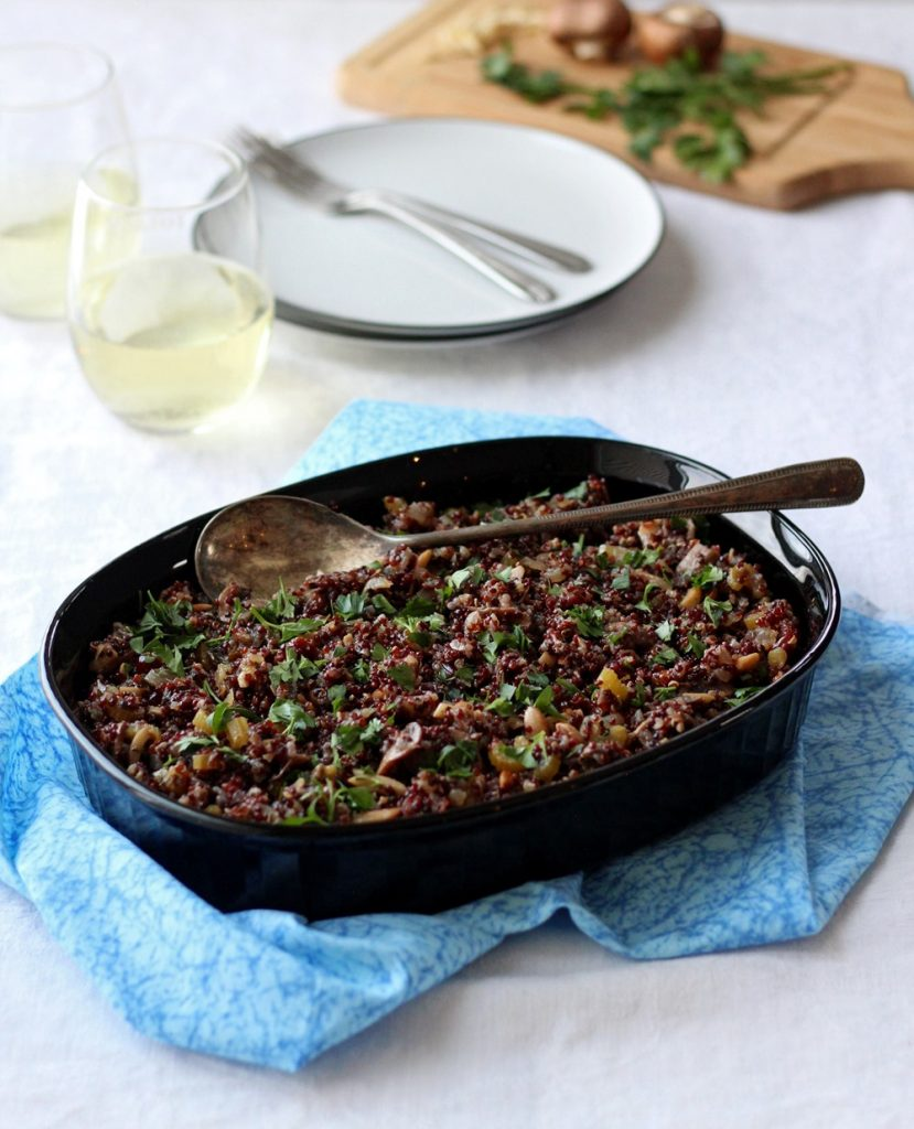 Quinoa stuffing in black dish on blue cloth with glasses on wine in background