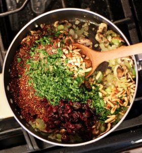 onions, mushrooms, celery, quinoa, dried cranberries, almonds, and seasonings in sauce pan with wooden spoon