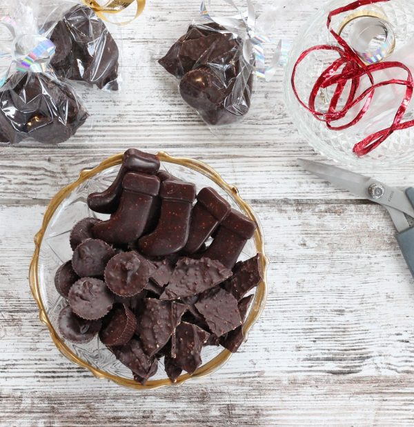 dark chocolate candies in glass bowl against white wood background