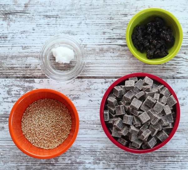 Coconut oil, dried cherries, dry quinoa, and dark chocolate chips in bowls on white wood background