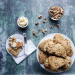 Baked scones on a white plate with a small bowl of walnuts nearby