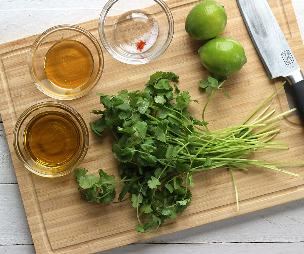 Ingredients for cilantro lime vinaigrette on a wood cutting board