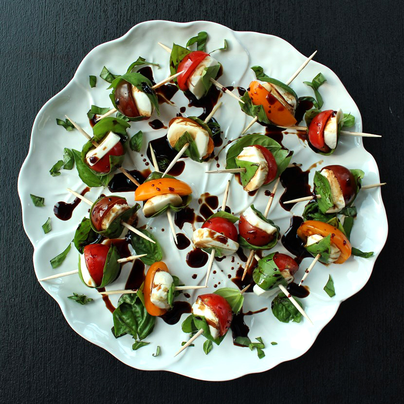 looking down on white plate with skewers of cherry tomatoes and fresh mozzarella wrapped with fresh basil leaves