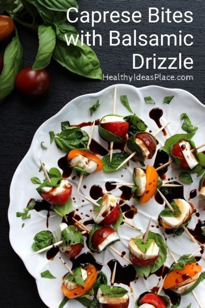 fresh basil leaves wrapped around cherry tomatoes and mozzarella on white plate