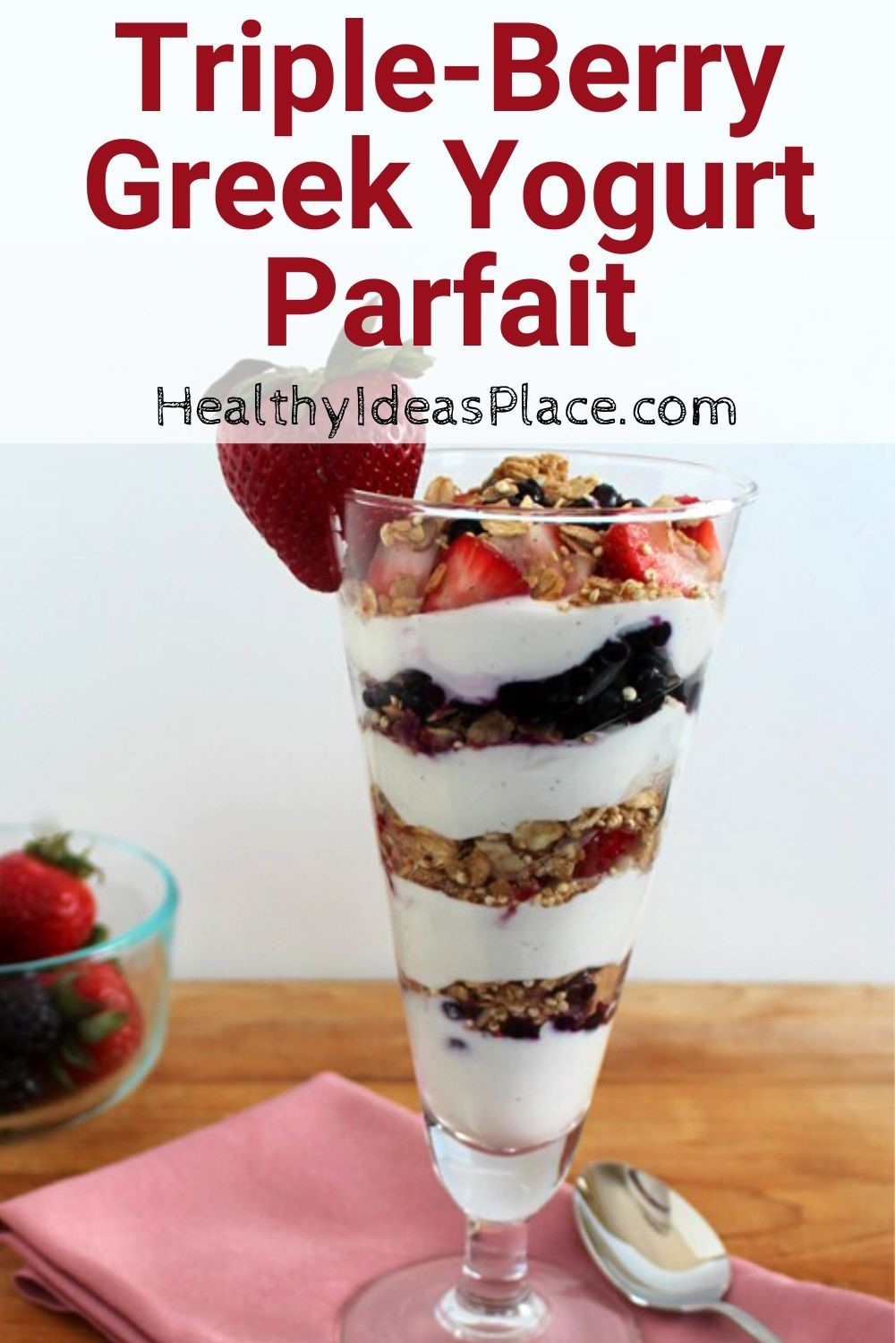 yogurt layered with berries and granola in fluted clear glass