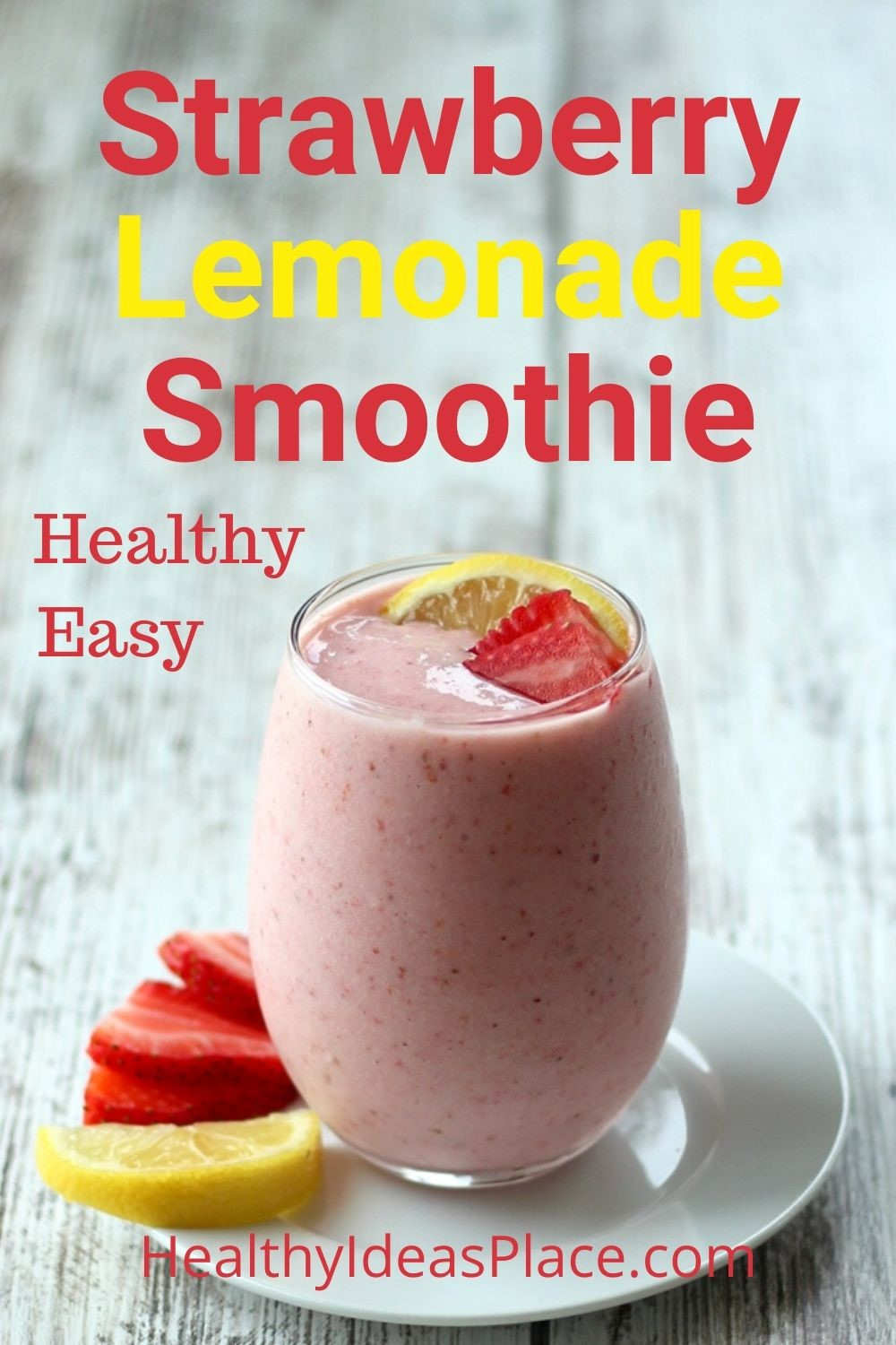 pink smoothie with strawberries and lemon in a clear glass