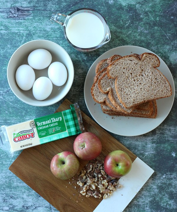 Eggs in bowl, milk, bread on plate, cheese, three apples, and chopped walnuts
