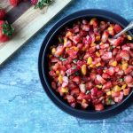 Diced strawberries, onions, and mango as a salsa in a black bowl