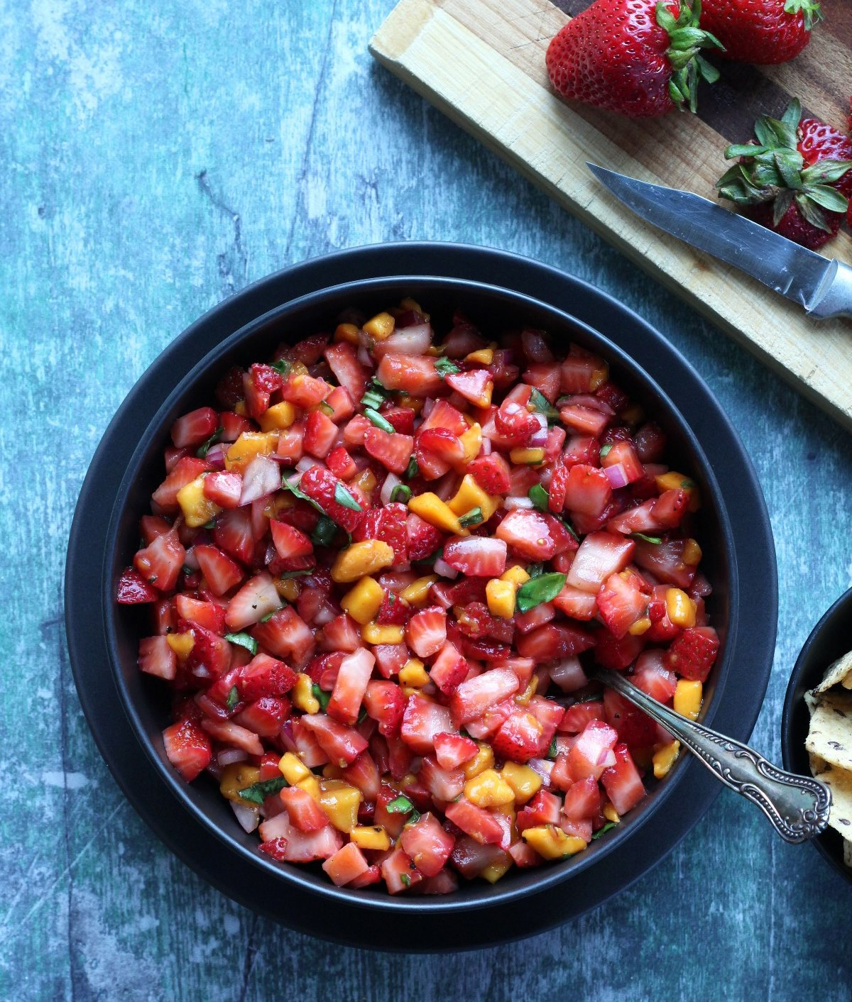 Diced strawberries as a salsa in a black bowl on a greenish background
